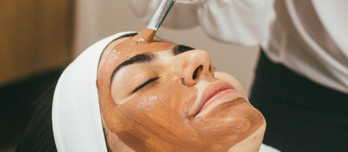 Beauty therapist applying face mask to woman